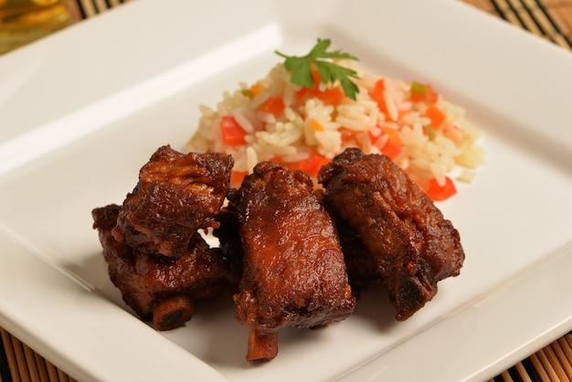 Блюдо с запеченными свиными ребрышками и белым рисом с овощами.