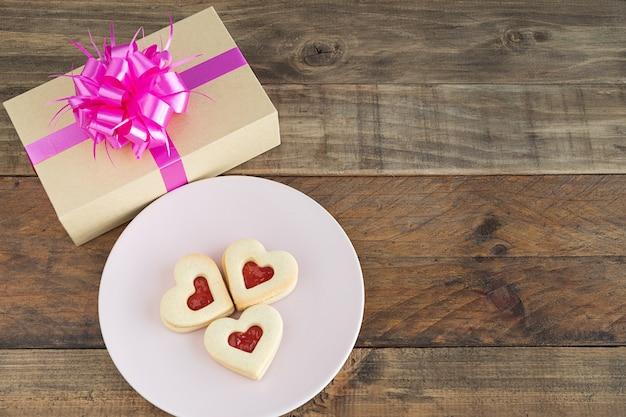 Блюдо с тремя печеньями в форме сердца на деревянной основе. концепция день святого валентина