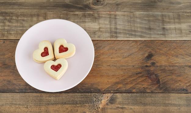 Блюдо с тремя печеньями в форме сердца на деревянной основе. скопируйте пространство. концепция день святого валентина, день матери, юбилей.
