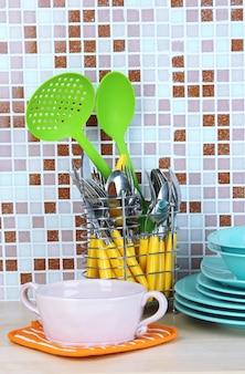 Посуда и столовые приборы на кухне на столе на фоне мозаичной плитки