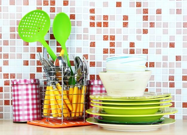 Посуда и столовые приборы на кухне на столе на мозаичной плитке