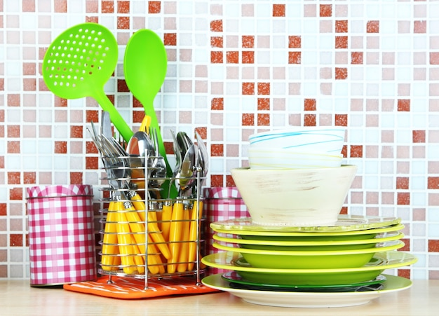 Dishes and cutlery in kitchen on table on mosaic tiles