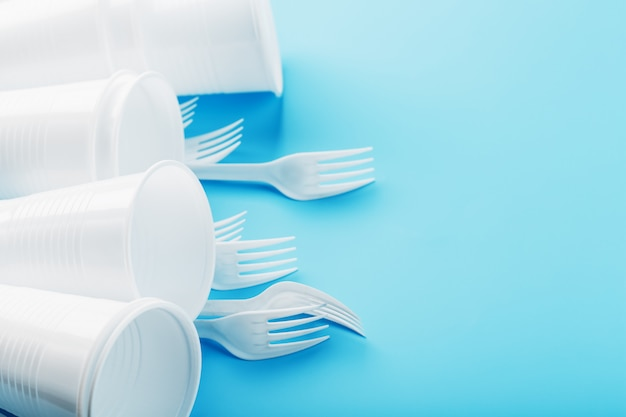 Dishes made of white plastic on a blue wall.