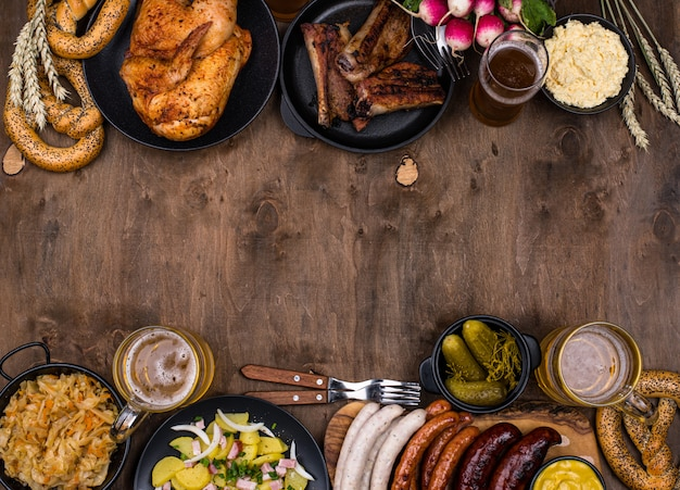 Dishes with beer, pretzel and sausage on wooden background