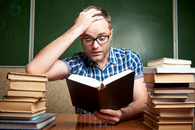 A disheveled tired unshaven young man with glasses holds his head and reads a book at the table