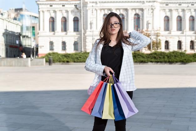 쇼핑 후 흐트러진 된 젊은 여자. 다채로운 가방으로 관광.