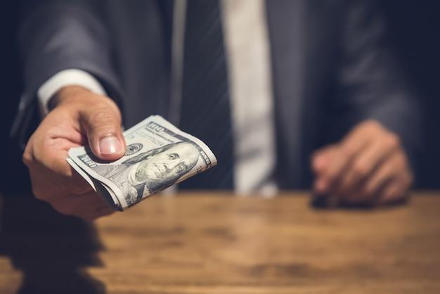 Dishonest businessman secretly giving away money in the dark