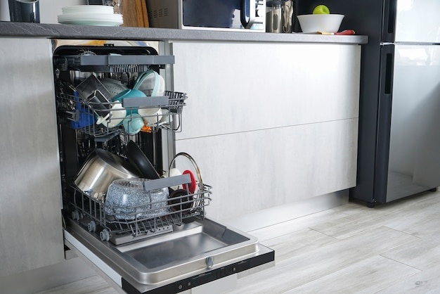 Dishwasher machine, open and loaded with dishes in the kitchen