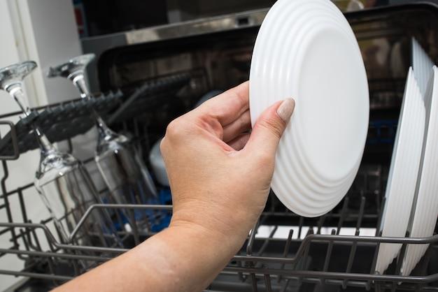 Таблетка для посудомоечной машины. уборка на кухне. мытье посуды в посудомоечной машине