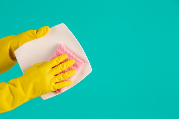 Dishwasher wearing yellow gloves on a blue .