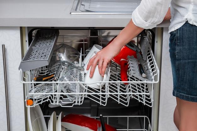 Посудомоечная машина с открытой дверцей и расширенными полками-корзинами с посудой и женщиной в короткой юбке, схватившей чашку