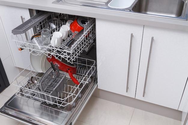 열린 문이 있는 식기 세척기와 주방의 실내에 접시가 있는 확장 선반