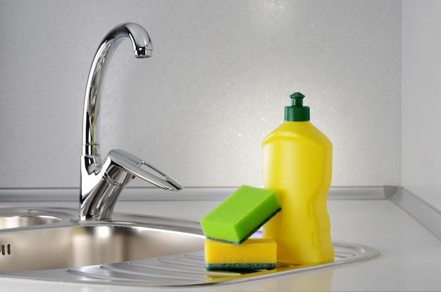 Жидкость для мытья посуды с губкой на кухонной раковине