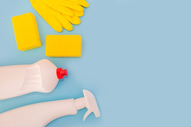Dishwashing sponges, gloves, spray and detergent in a bottle on a blue surface.