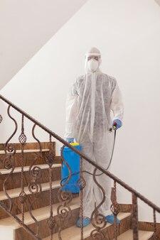Disinfectant working in protective suit spreading antibacterial against coronavirus.