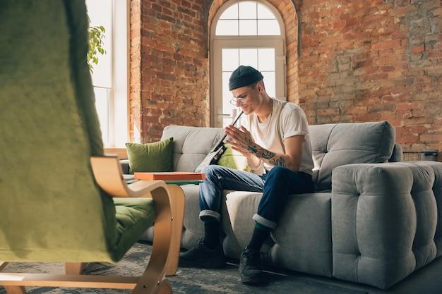 消毒。オンラインコース、スマートスクール中に自宅で勉強している男性。隔離された状態でクラスや職業を取得し、コロナウイルスの拡散を隔離します。ノートパソコン、スマートフォン、ヘッドホンを使用。