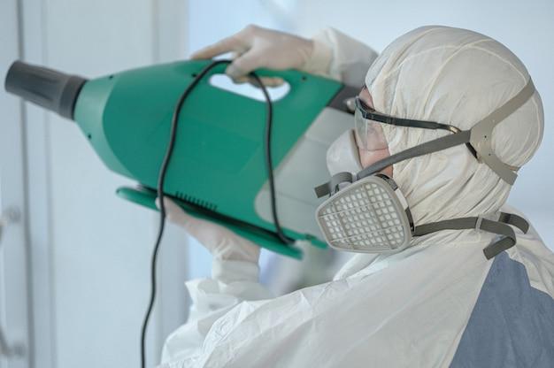 Covid-19, 흰색 방 광복을 입은 사람, 사무실 소독, 코로나 바이러스 개념을 예방하기위한 사무실 소독