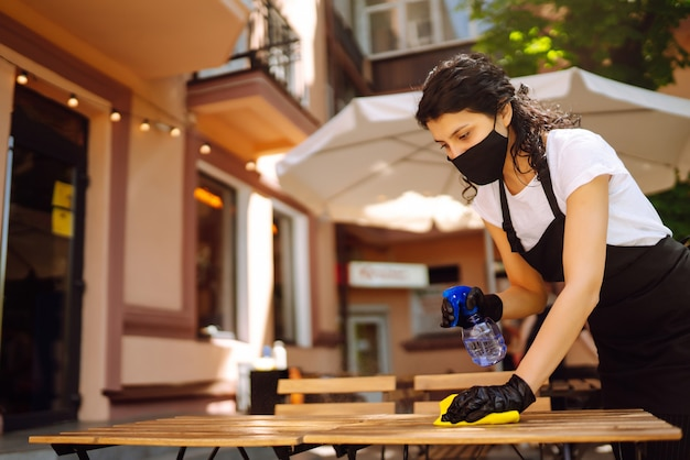 Disinfecting to prevent covid-19. waitress cleaning the table.