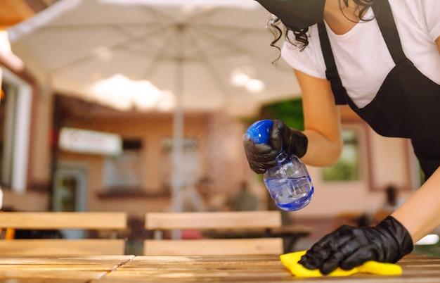 Covid-19を防ぐための消毒。テーブルを掃除するウェイトレス。