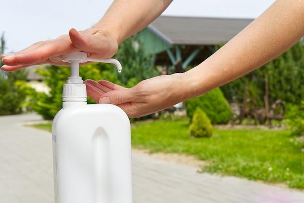 ホワイトボトルのクローズアップから女性の手の消毒剤を消毒します。熱狂的な時代のウイルスや病気に対する受動的保護の概念。