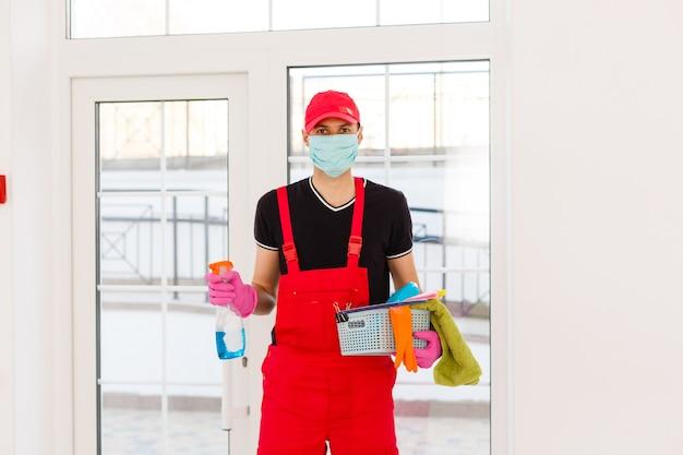 Дезинфекция для уничтожения вирусов. рабочий в защитной маске, чистящей интерьер, с помощью химических агентов, чтобы остановить распространение вирусных инфекций.