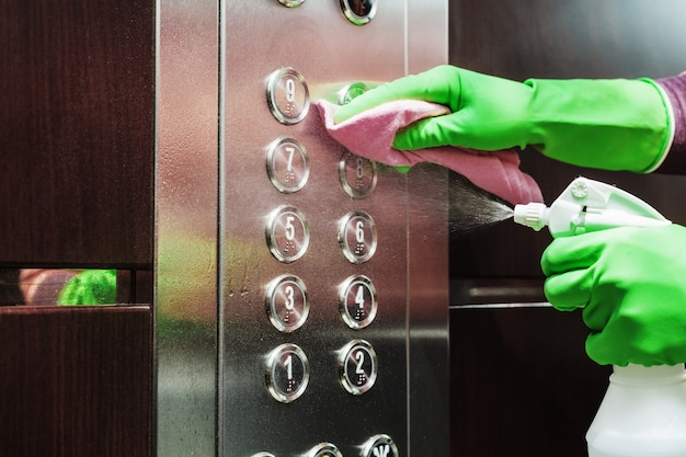 Disinfection and hygienic care using alcohol spray on the elevator button.