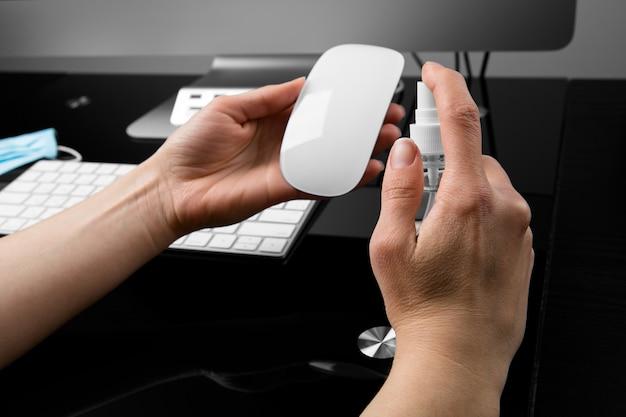 Дезинфекция компьютерной мыши антисептиком. концепция дезинфекции на рабочем месте.