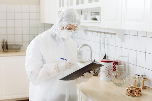 보호 복의 청소 제품으로 집안 소독, 코로나 바이러스 covid-19의 표면 처리. 주방 소독기가 작동 중입니다.