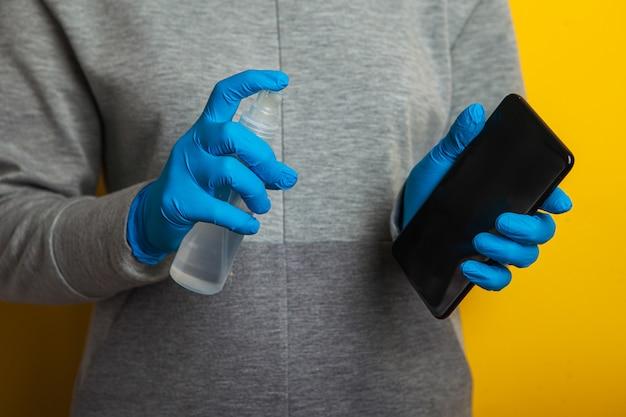 Дезинфекция телефона. женщина в резиновых перчатках держит в руках телефон и дезинфектор.