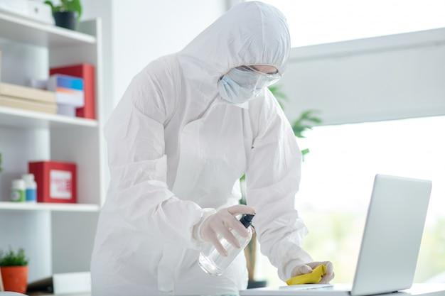 消毒。表面消毒を行う防護作業服の人
