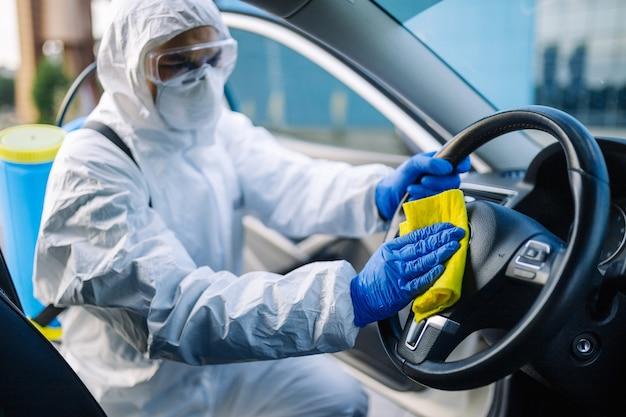 소독 전문가가 자동차의 핸들을 청소합니다.
