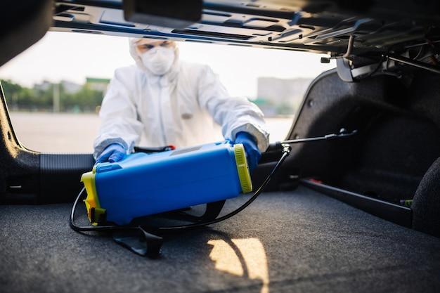 소독 서비스 직원이 스프레이 장비를 차량 트렁크에 넣습니다. 보호 복, 마스크 및 장갑을 착용 한 남자가 차에서 위생 스프레이를 꺼냅니다. 청소 및 covid-19 예방.