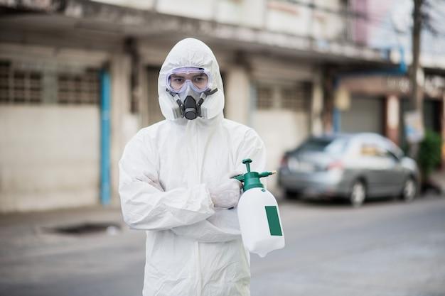 Специалист по дезинфекции человек в костюме средств индивидуальной защиты (ppe), перчатках, маске и защитной маске, уборка карантинной зоны с помощью флакона дезинфицирующего средства под давлением для удаления коронавируса