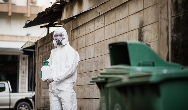 Disinfection specialist man in personal protective equipment (ppe) suit, gloves, mask and face shield, cleaning quarantine area with a bottle of pressurized spray disinfectant to remove coronavirus