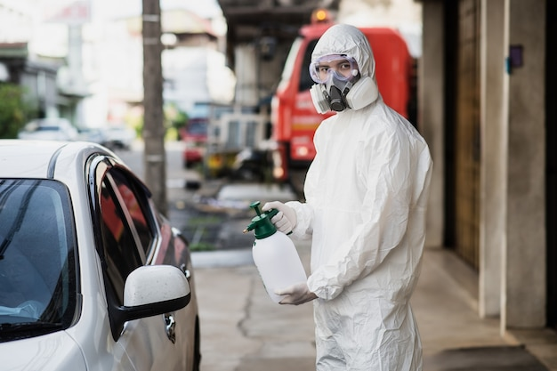 개인 보호 장비(pp), 장갑, 마스크, 투명 안경을 쓴 소독 전문가 남자, covid-19를 제거하기 위해 가압 스프레이 소독제 병으로 차를 청소합니다.