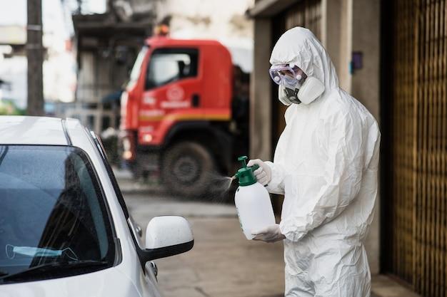 個人用保護具(ppe)スーツ、手袋、マスク、透明な眼鏡を着用し、covid-19を除去するために加圧スプレー消毒剤のボトルで車を掃除する消毒専門家の男性