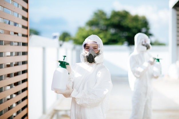 Disinfection specialist team in personal protective equipment (ppe) suit, gloves, mask and face shield, cleaning quarantine area with a bottle of pressurized spray disinfectant to remove covid-19