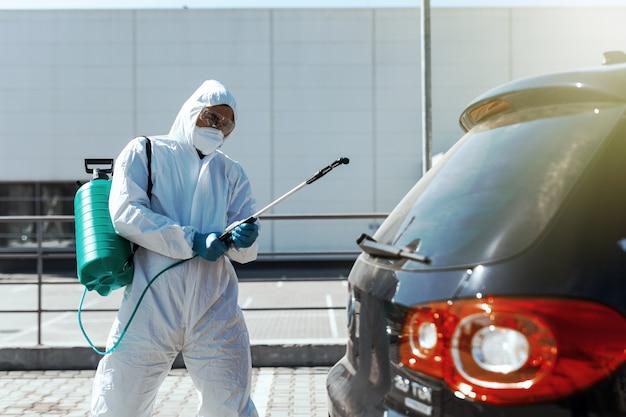 防護服を着た消毒器が車の汚染された領域を消毒し、コロナウイルスを防ぎます。健康管理。