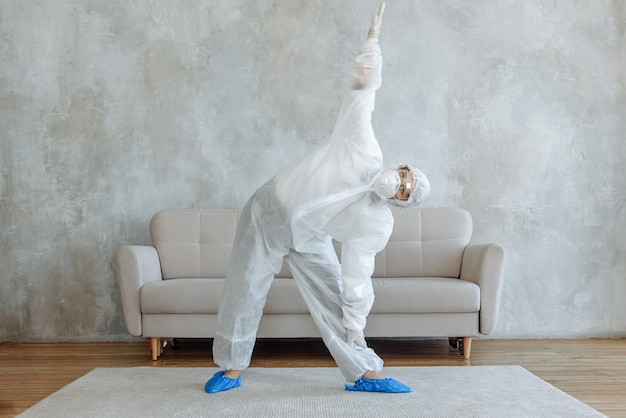 A disinfector in a protective suit at home in the room plays sports in front of a sofa.