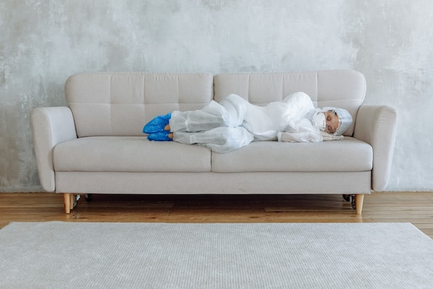 Disinfector woman in white overalls  gloves and a respirator resting or sleeping on the couch