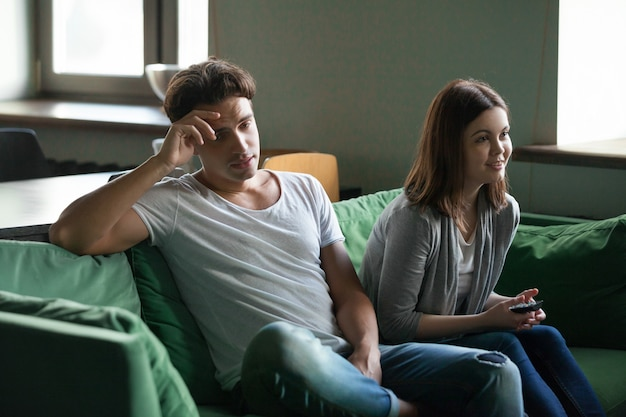 Disinterested boyfriend getting bored while excited girlfriend watching tv series