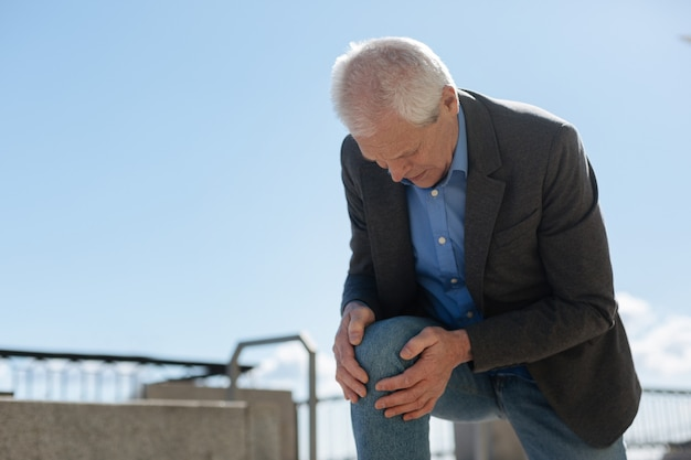 Dismal frustrated old man raising himself onto his knee holding hands on it while feeling terrible pain