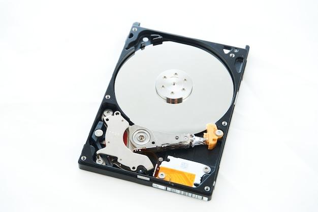 白で隔離の解体されたコンピューターのハードドライブ