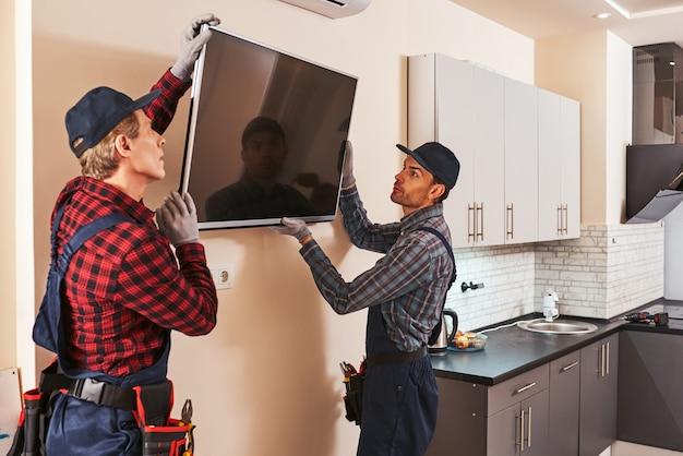 電子機器の解体2人の技術者がキッチンのプラズマを除去