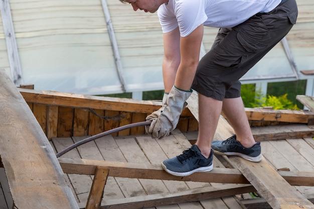 屋根を解体する。労働者は屋根から古い板を取り除き、家は改装中です。
