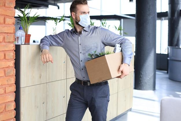 전염병 코로나바이러스 covid-19의 해고 직원. 사무실에서 사무용품을 들고 출근하는 해고된 노동자