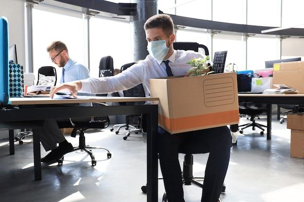전염병 코로나바이러스 covid-19의 해고 직원. 슬픈 해고된 노동자가 사무실에서 사무용품을 들고 있다