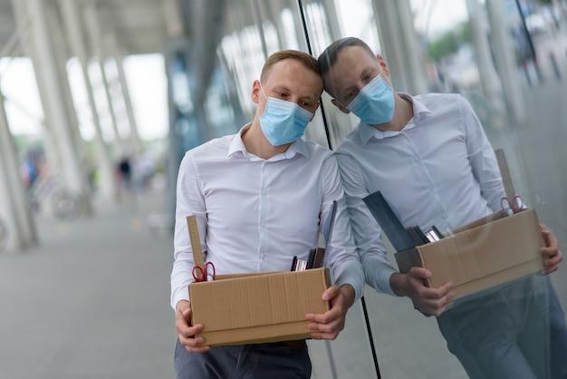 Увольнение работника из-за эпидемии коронавируса. уволенный сотрудник сперся к стене офиса со своими канцелярскими товарами.