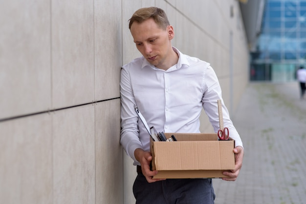 解雇されたサラリーマンは彼の文房具の箱を保持しています。閉じる。無料の場所。
