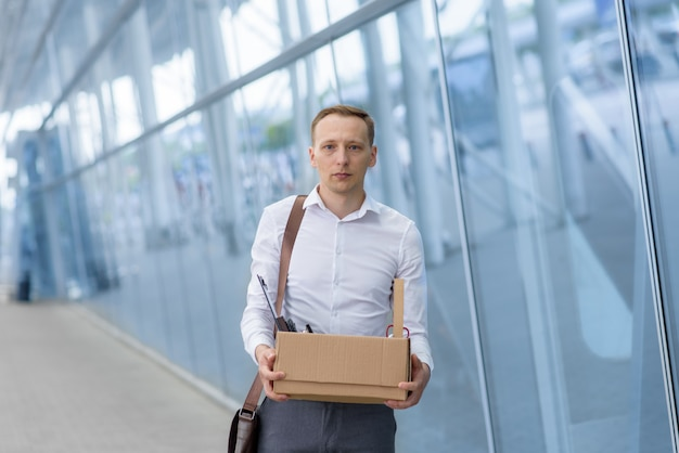 Dismissed office worker holds stationery in his hands in a cardboard box.